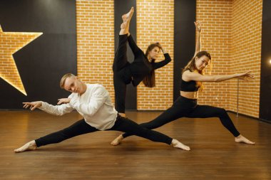 Contemporary dance performers poses in studio. Female and male dancers  training in class, modern grace dancing, stretching exercise