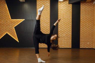 Contemporary dance performer, woman in studio, body flexibility. Dancer on workout in class, modern ballet, elegance dancing, stretching exercise