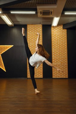 Contemporary dance performer, woman in studio, body flexibility. Dancer on workout in class, modern ballet
