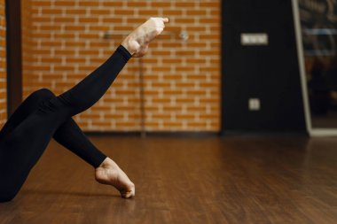 Female contemporary dance performer legs flexibility, stretching exercise, women on workout in studio. Dancers training in class, modern ballet, elegance dancing