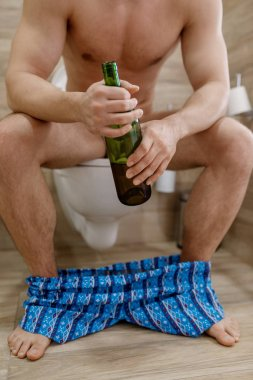 Hangover man with bottle of wine sitting on the toilet in bathroom. Hungover male person, headache and depression, bad morning