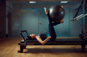 Štíhlé děvče ve sportovním oblečení, pilates trénink s míčem na cvičebním stroji v tělocvičně. Fitness workuot ve sportovním klubu. Atletická žena, aerobik uvnitř, roztažení těla