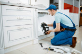 Photo Male plumber in uniform installing disposer in the kitchen. Handywoman with toolbag repair sink, sanitary equipment service at home