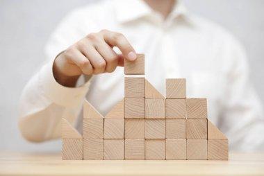 Man's hand stacking wooden blocks. Business development concept stock vector