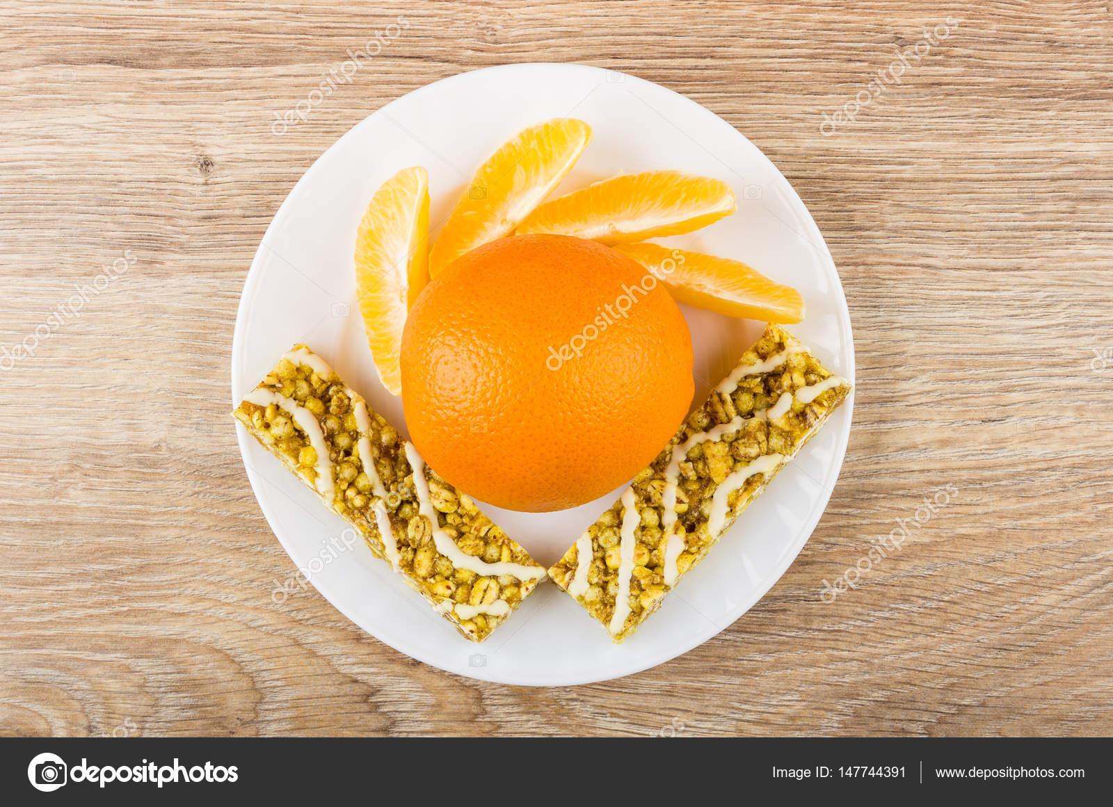 Scheiben von Orange und Granola Bars mit Getreide in Platte ...