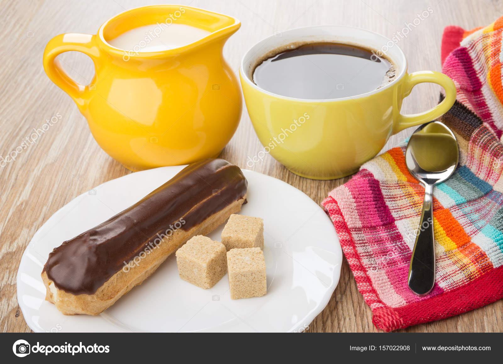 Eclair Mit Schokolade Klumpig Zucker In Platte Schwarzer Kaffee