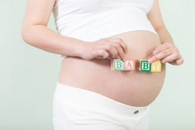 young pretty pregnant woman with cubes