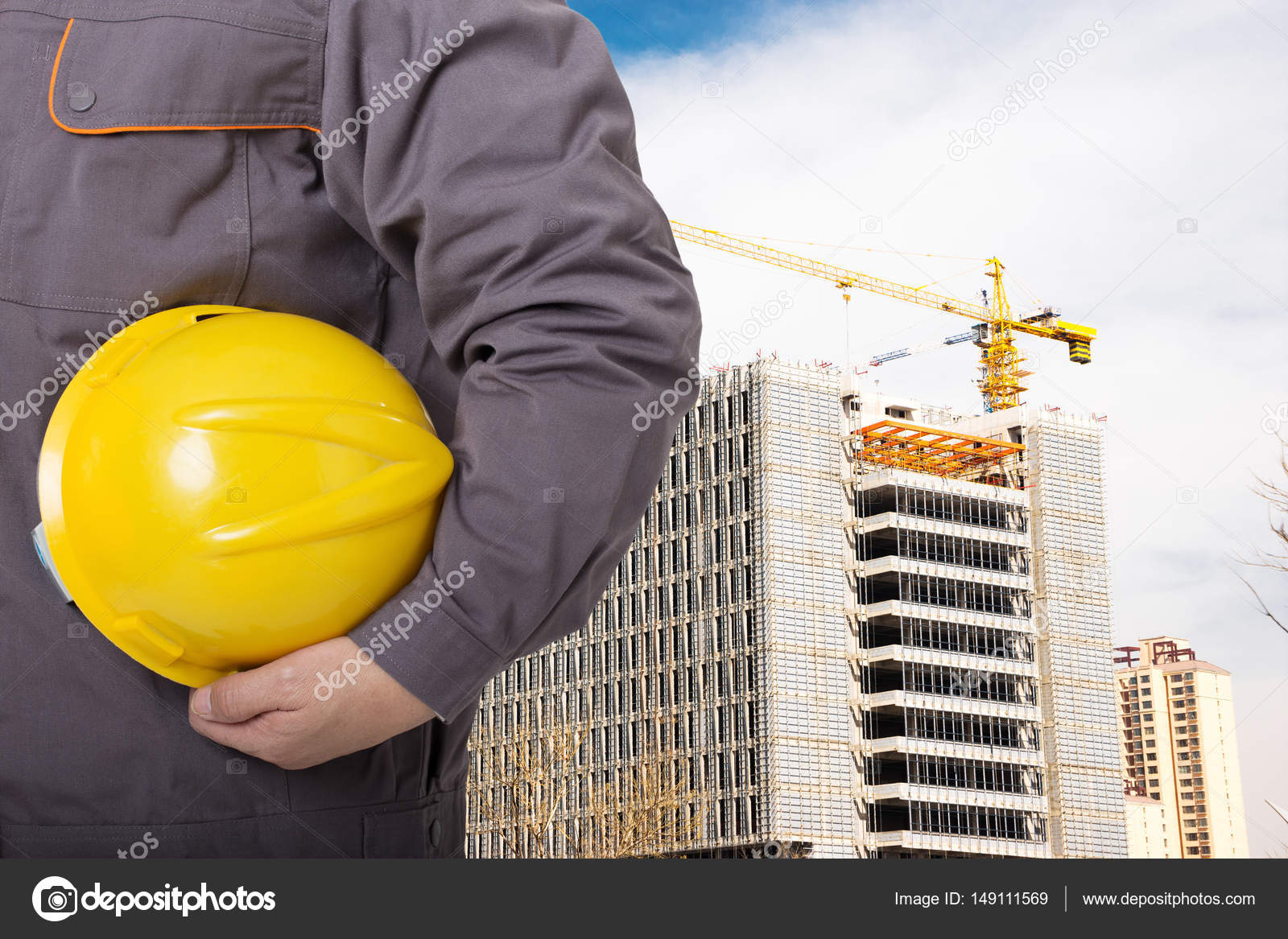 chinese man technician with yellow helmet standing front of constructions site photo by zhudifeng