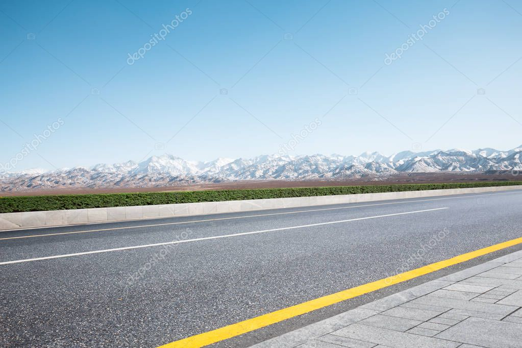 empty road with snow mountains
