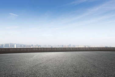 empty asphalt road and cityscape of Shaoxing in blue foggy sky