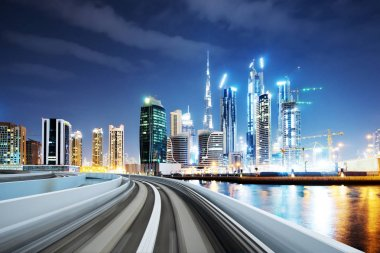 blurry empty asphalt road and modern buildings in midtown of Dubai in cloud sky at night