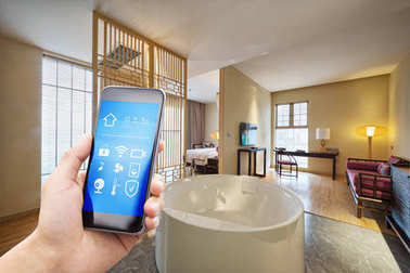 smartphone with smart home and modern bathroom in hotel