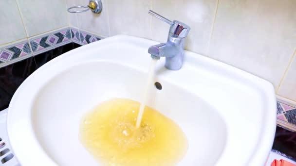 proud špinavé vody z kohoutku teče do dřezu jako ukázka nechutné práce veřejných služeb