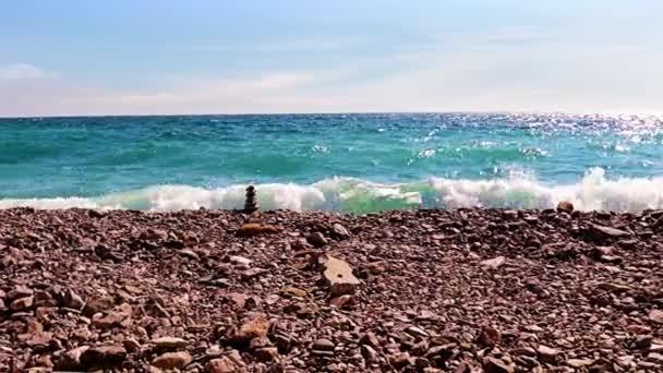 pyramida z kamení na oblázkové pláži na mořském pobřeží pod modrou oblohou