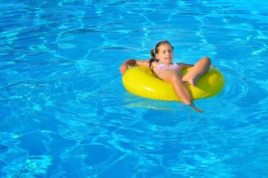 Real toddler girl relaxing at swimming pool