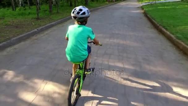Mladý chlapec, jízda na kole v přilbě na silnici zadní pohled.