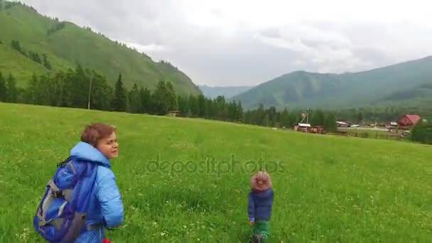 Děti pobíhají v zelené louce vysokou vesnice v horách