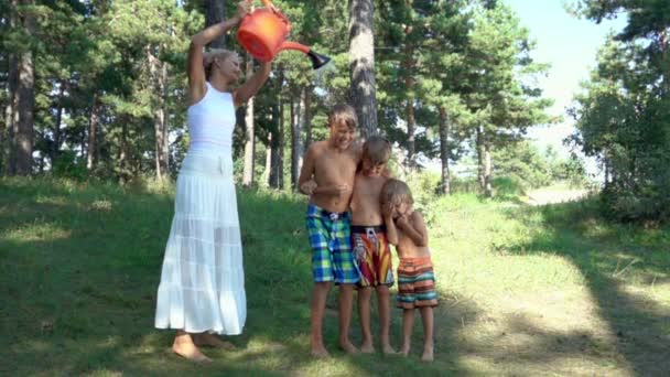 Junge Frau gießt Wasser aus einer Gießkanne auf Kinder in Zeitlupe