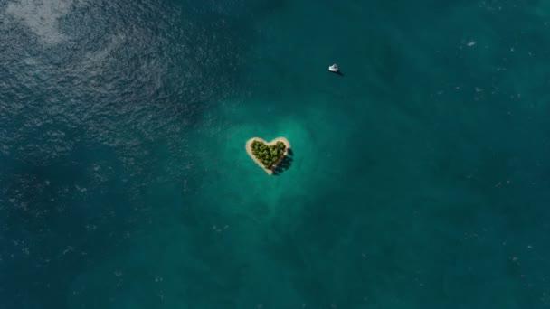 Insel in Herzform im Ozean und fliegendes Flugzeug