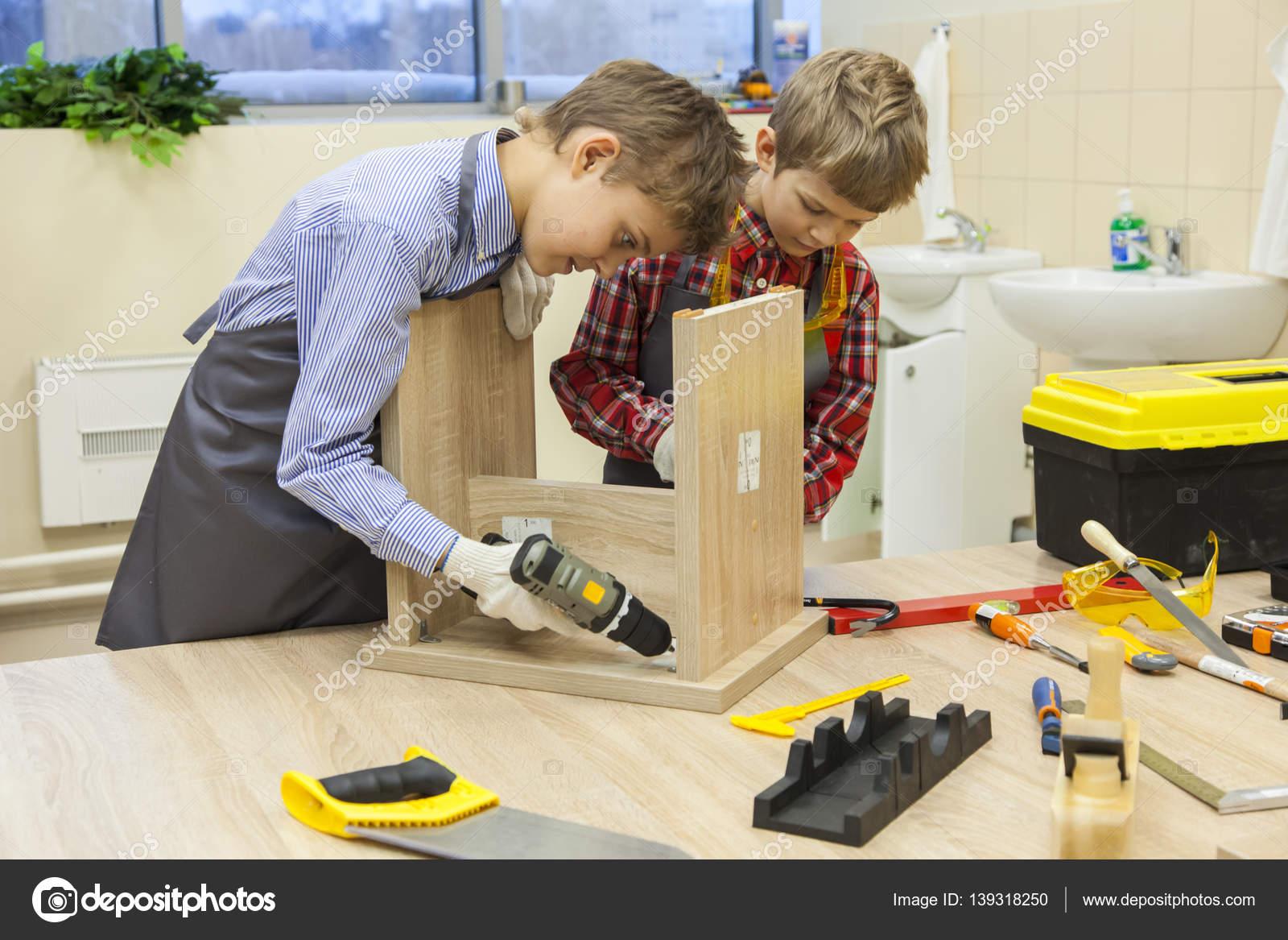 Ragazzi con cacciaviti e trapano riparazione sgabello in legno