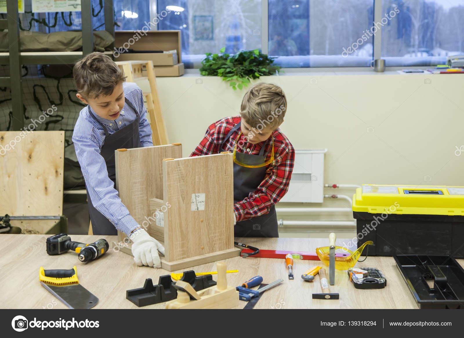 Giovani ragazzi di banco serraggio viti in sgabello in legno