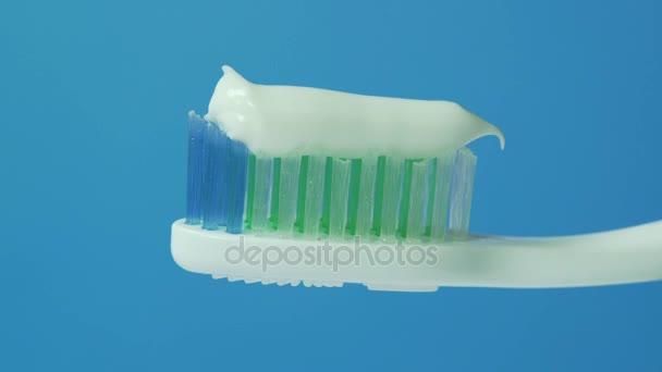 Zahnpasta wird auf eine Zahnbürste gepresst