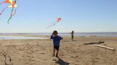 Boys running with kites at beach.