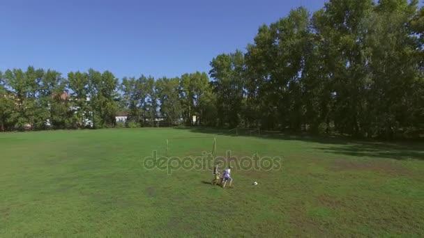 Anténa: tři děti hrají fotbal v zeleném poli