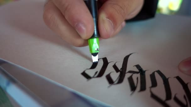 male hand writes with ink pen letters of the Latin alphabet