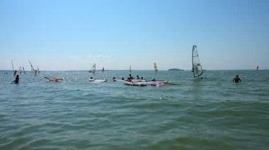 People having fun in sea and windsurfers surfing the wind in sunny day. Summer holidays. Festival of Sports and Leisure