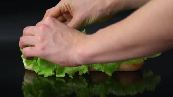 preparing fresh submarine sandwich with salami and lettuce on black background
