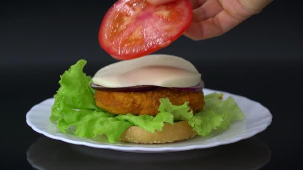 Aby chutné burger na bílé plotně proti černému pozadí. Domácí hamburger s kuřecího řízku, rajče, sýr, cibule a salátem