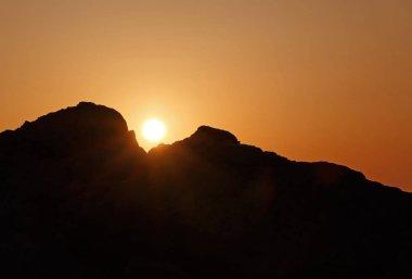 sun rising between two rocks