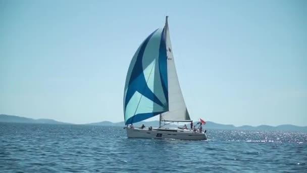 Jachta s pruhovanou plachtou se řítí do modrého hlubokého moře. Zpomalená regata. Středozemní moře.