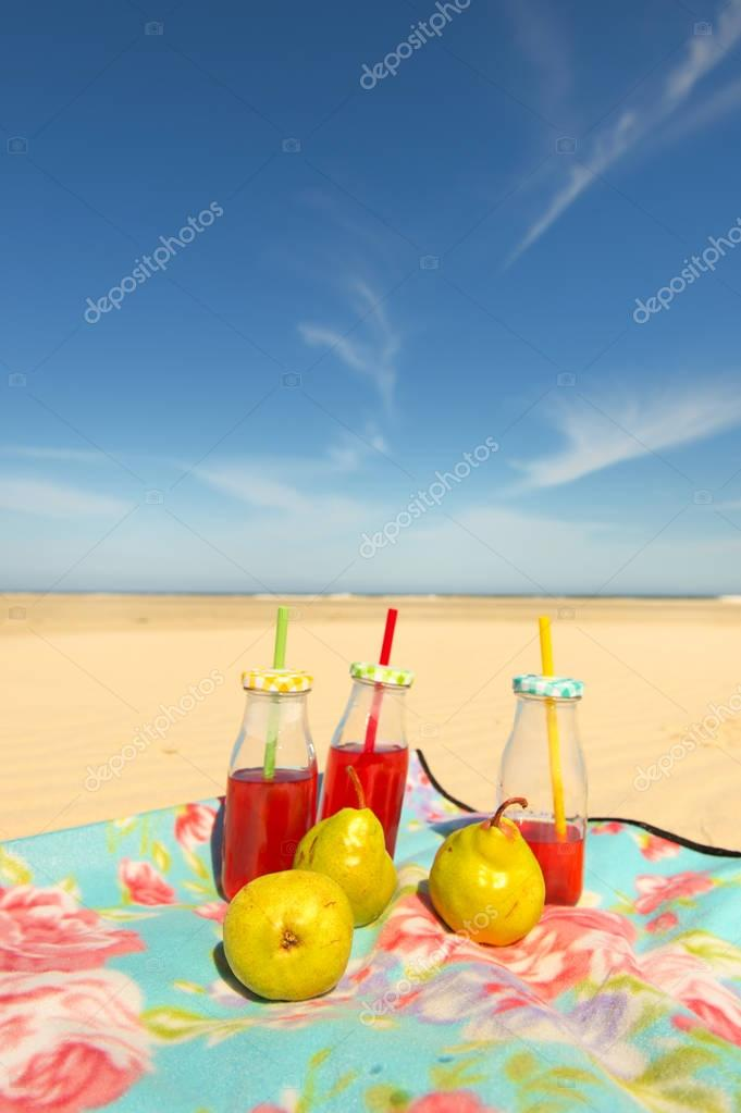 Bottles lemonade and fruit at beach
