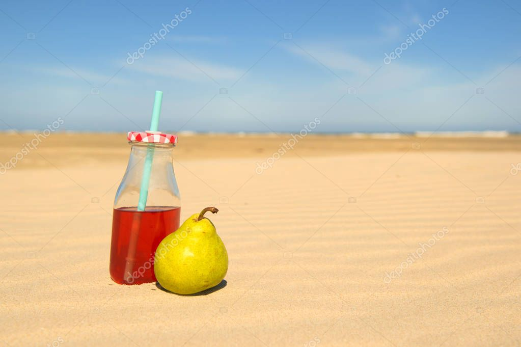 Bottle lemonade and fruit at beach