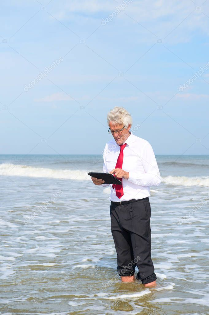 Business man working on tablet standing in the sea