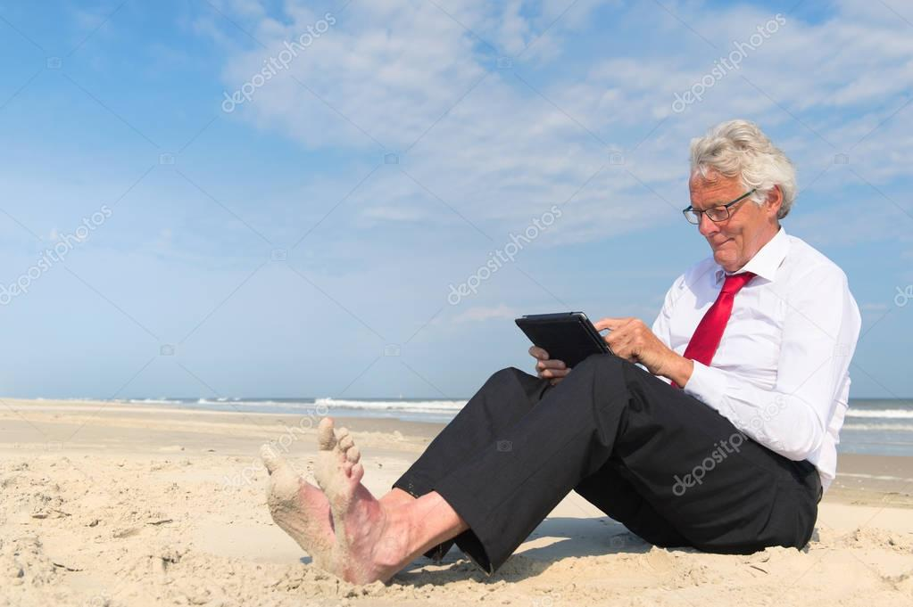 Business man working on tablet at the beach