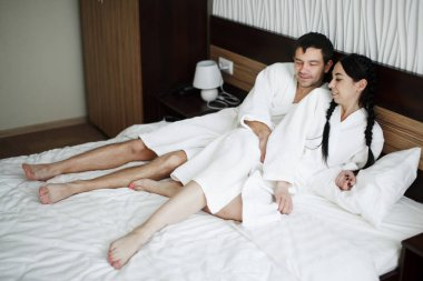 Young husband and wife of white coats play and smile in bed in a
