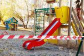 Farbenfroher leerer Spielplatz an einer Polizeikette