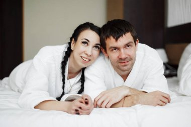 Young husband and wife of white coats play and smile in bed in a hotel room. Close up.