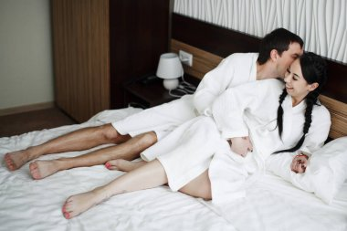 Young husband and wife of white coats play and smile in bed in a hotel room