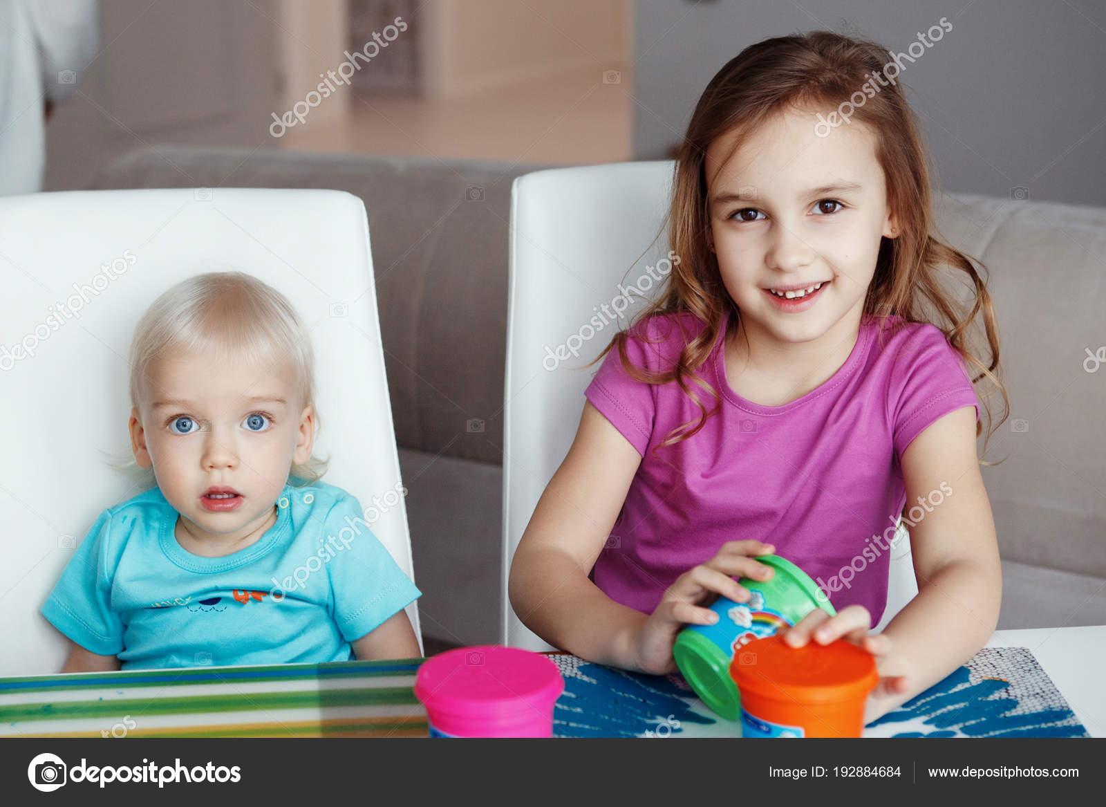 2118e34bc5f Δύο χαρούμενα παιδιά ξανθό αγόρι και κορίτσι παίζει κάθεται στο ...