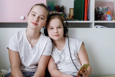 Two teenage girls in white t-shirts with headphones are sitting looking at the camera. Modern youth at home.