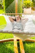 Dívka, relaxační a poslouchání hudby v houpací síti