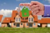Schlüssel in der Hand des Immobilienmaklers als Angebot für neues Eigenheim