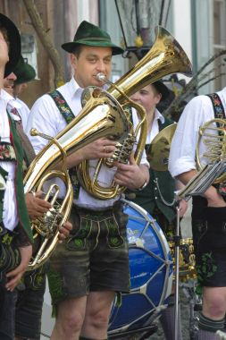 In many villages of Bavaria it is historical customs to erect an decorated high tree at 1. May by local men, clothed in traditional bavarian dress with musicians of an brass band