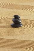Giardino giapponese di Zen con pietre impilate in sabbia martellata