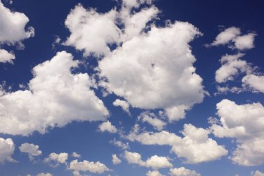 cumulus clouds at blue summer sky