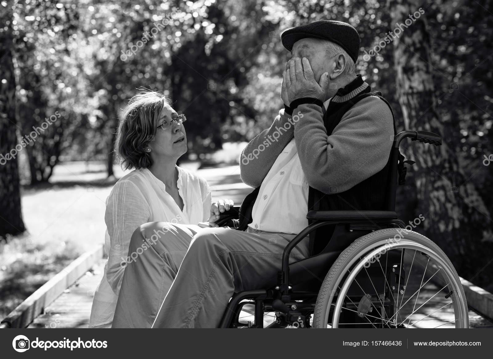 Triste Uomo Anziano Sulla Sedia A Rotelle E Giovane Donna